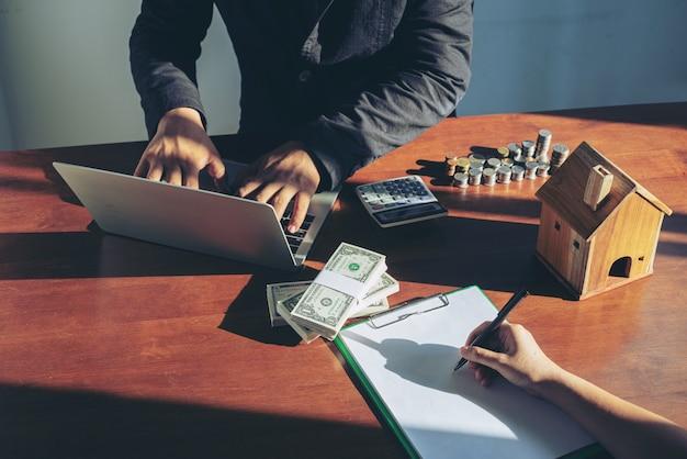 住宅と不動産価格の概念を売買するビジネスマン。契約書に署名するビジネス