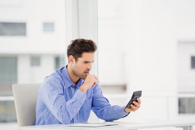 Businessman calculating accounts on a calculator