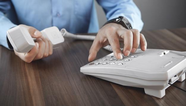 ビジネスマンがオフィスの電話で呼び出します。連絡先の概念