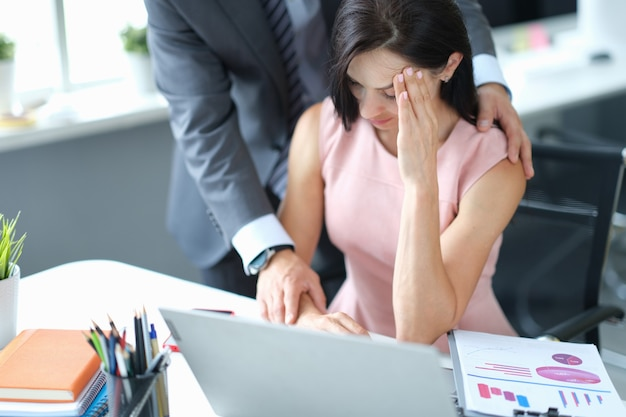 Businessman calming down young fatigue colleague at workplace