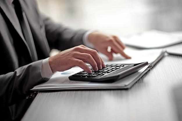 ビジネスマンは、計算機を使用して利益を計算できます