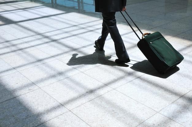 사업가는 가방을 들고 현대 공항 환경에서 가벼운 포장 통로로 앞으로 나아갑니다.