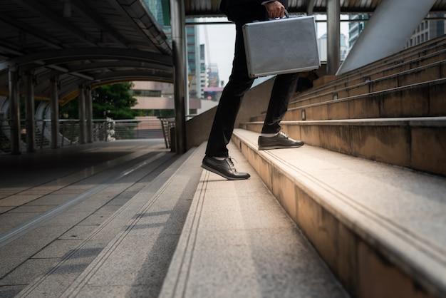 ブリーフケースを運ぶビジネスマンは階段を上ります。