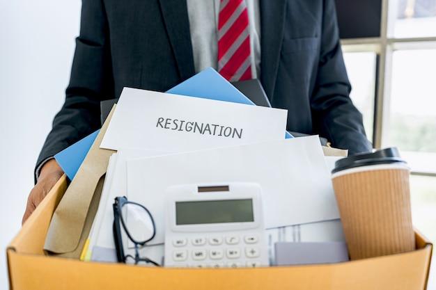 現代のオフィスで辞任するために茶色の段ボール箱に彼のすべての個人を運ぶビジネスマン
