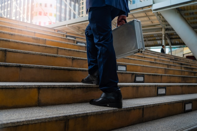 Businessman carrying a briefcase walk up stair to discuss business at the office.