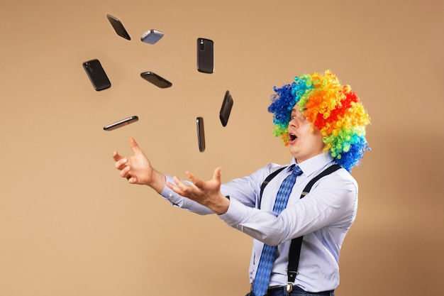 Businessman catching mobile phones falling from above. close-up portrait of business man in clown wig. business concept