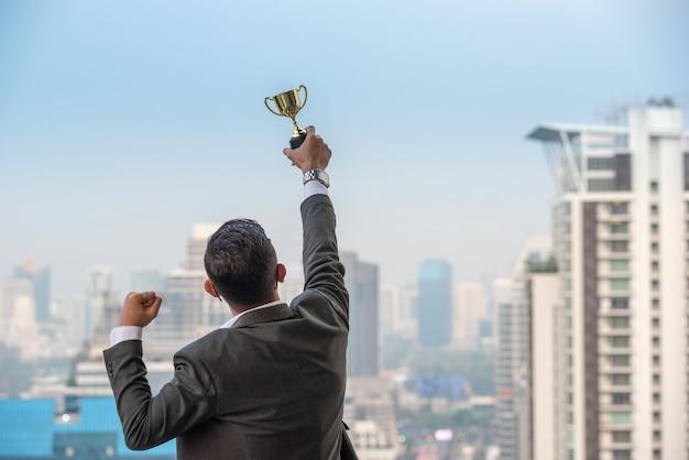 Businessman celebrating with trophy