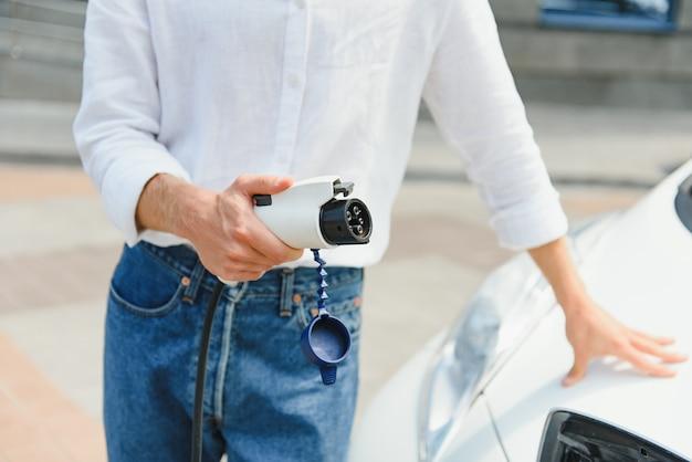 Бизнесмен, заряжающий электромобиль