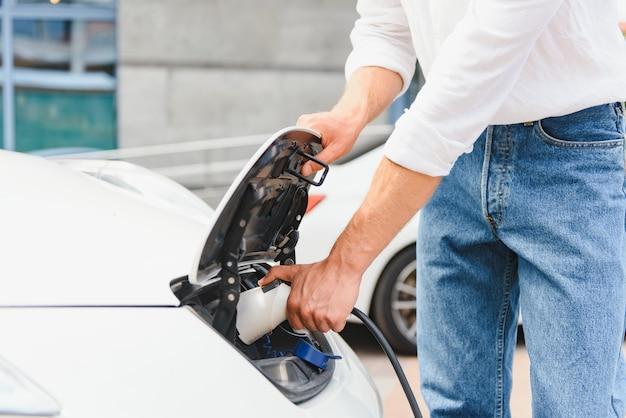 전기 자동차를 충전 하는 사업가