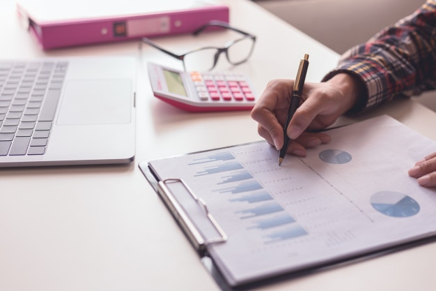 Businessman check about cost and doing finance graph report at office