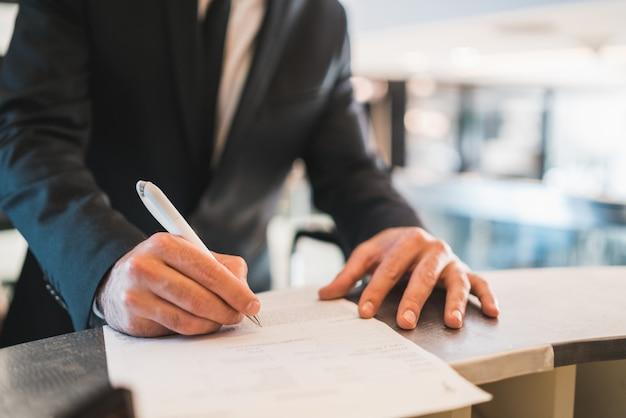 Регистрация бизнесмена на стойке регистрации отеля.