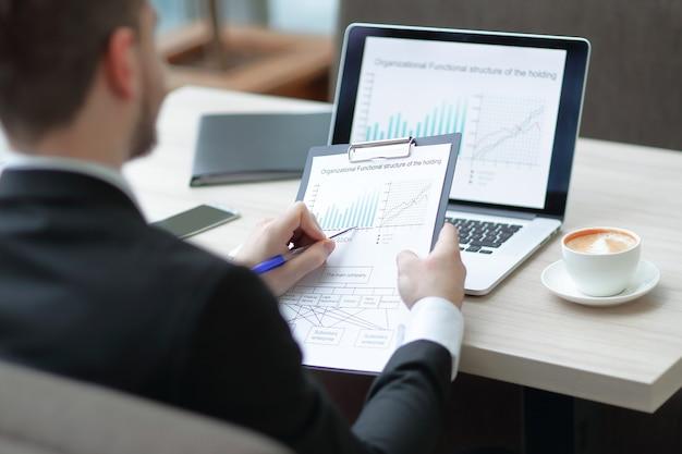 Бизнесмен проверки финансовых документов, сидя за столом