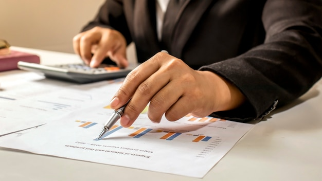 ビジネスマンは、オフィスワークと仕事での成功の仕事の概念で財務報告をチェックします