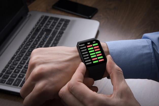 スマートウォッチから外国為替取引、株式市場価格をチェックするビジネスマン。 fintechインテリジェンステクノロジーは、証券取引所取引への金融投資に関するユーザーの柔軟でデジタルなソリューションを可能にします。