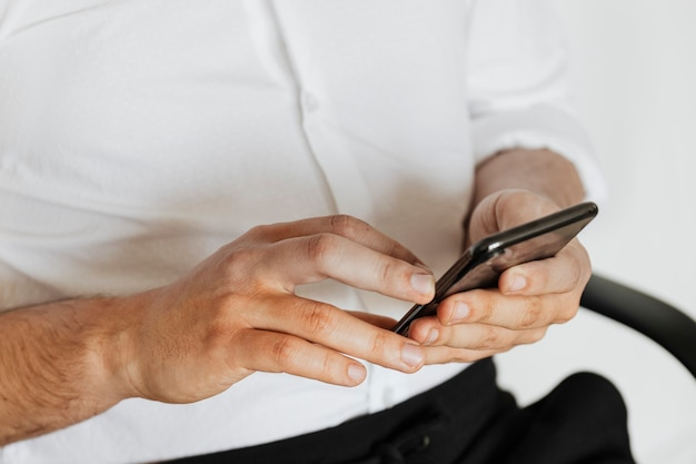 電話で彼のソーシャルメディアアカウントとメッセージをチェックするビジネスマン