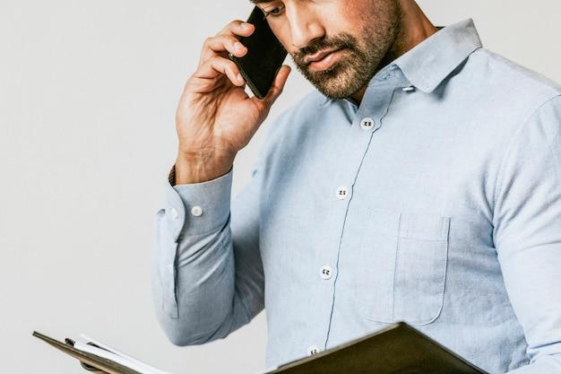 電話で話している間彼のプランナーをチェックするビジネスマン