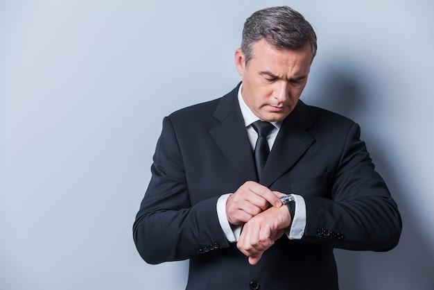 시간을 확인하는 사업가. 자신의 시계를보고 회색 배경에 서있는 동안 시간을 확인하는 formalwear에서 자신감이 성숙한 남자
