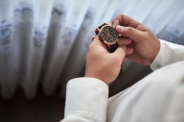 彼の腕時計で時間をチェックするビジネスマン