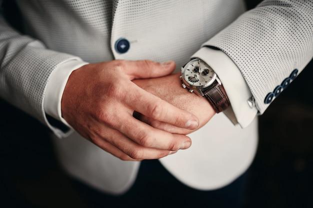 그의 손목 시계에 시간을 확인하는 사업