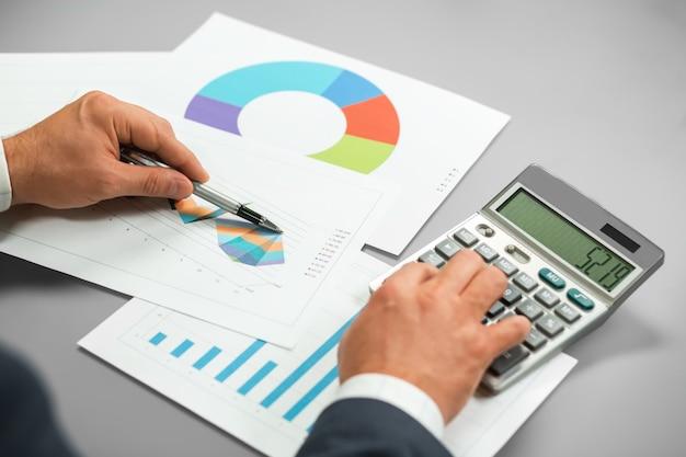 판매 보고서를 확인 하는 사업가. 숫자 비교. 신중한 계산. 시장이 성장하고 있습니다.
