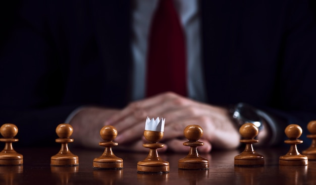 Businessman at a chessboard in front of a pawn with a paper crown on his head