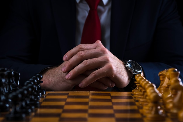 A businessman at a chessboard with figures lined up in their places