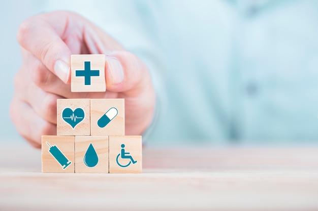 ビジネスマンは木製のブロック、ヘルスケアおよび医療保険のコンセプトに絵文字アイコン医療医療シンボルを選択します