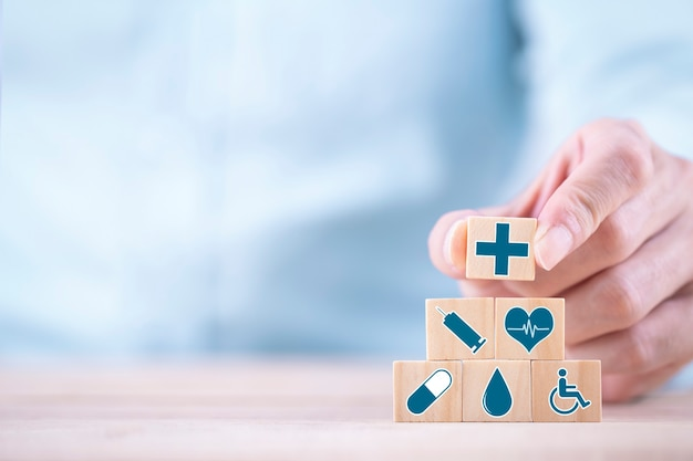 ビジネスマンは、木製のブロック、ヘルスケアと医療保険の概念に絵文字アイコンヘルスケア医療シンボルを選択します