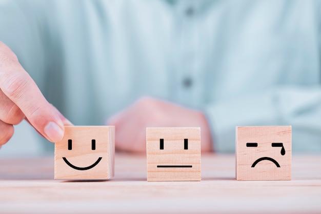 ビジネスマンが笑顔の絵文字アイコンに直面する木製のブロック、サービスおよび顧客満足度調査の概念に幸せなシンボルに直面