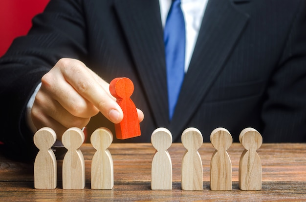 Businessman chooses a person from the team. the best employee, leader. leadership and promotion.