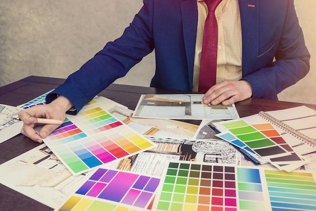 ビジネスマンは、改装後に彼のモダンなアパートの色を選択します。カラーパレット付きの家のスケッチ