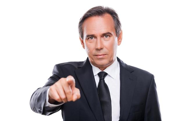 Бизнесмен, выбирающий вас. портрет уверенного в себе зрелого мужчины в формальной одежде, смотрящего в камеру и указывающего на вас, стоя на белом фоне