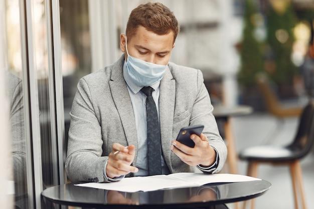 Uomo d'affari in una città. persona in maschera. ragazzo con documenti e telefono;