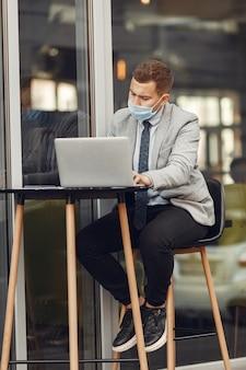 Uomo d'affari in una città. persona in maschera. ragazzo con laptop.