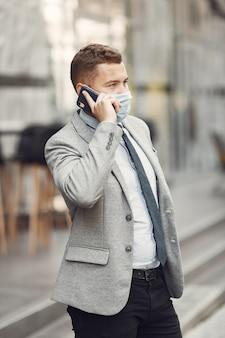 Uomo d'affari in una città. persona in maschera. ragazzo con il telefono.
