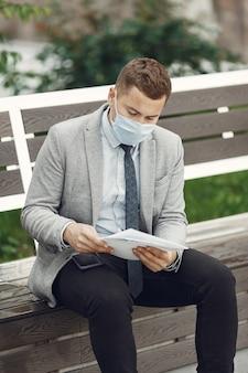 Uomo d'affari in una città. persona in maschera.
