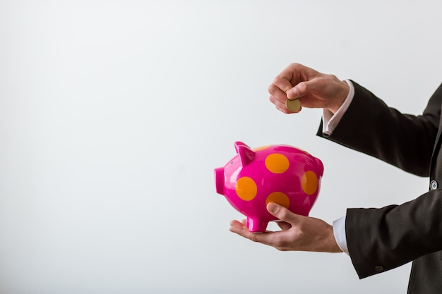 Businessman in classic suit holding a piggy bank and coin.