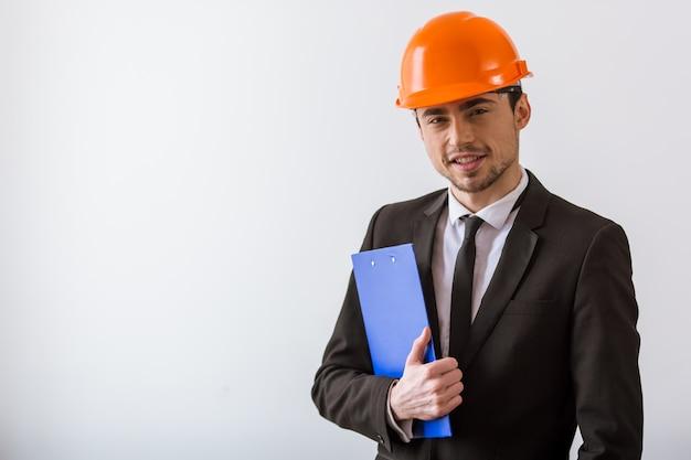 Businessman in classic suit and orange helmet smiling.