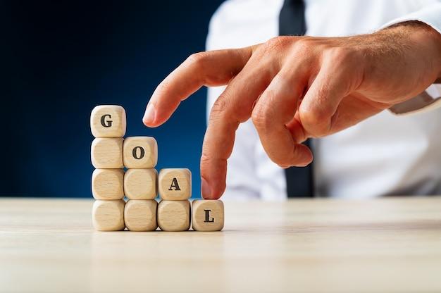ビジネスビジョンと野心の概念的なイメージで目標という言葉を綴る階段を指で登るビジネスマン。