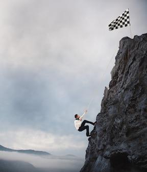 ビジネスマンは旗に到達するために山に登る。達成ビジネス目標と困難なキャリアコンセプト