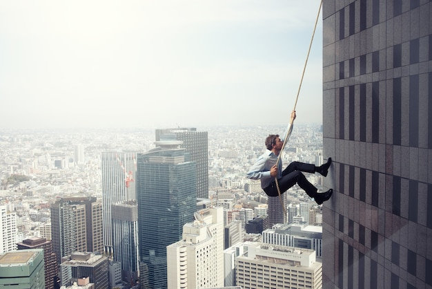 Бизнесмен поднимается по веревке на высокое здание