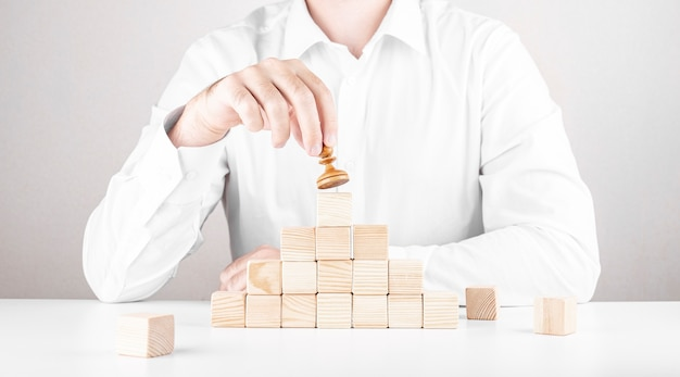 Businessman climbs the career ladder. business concept from cubes and pawn.