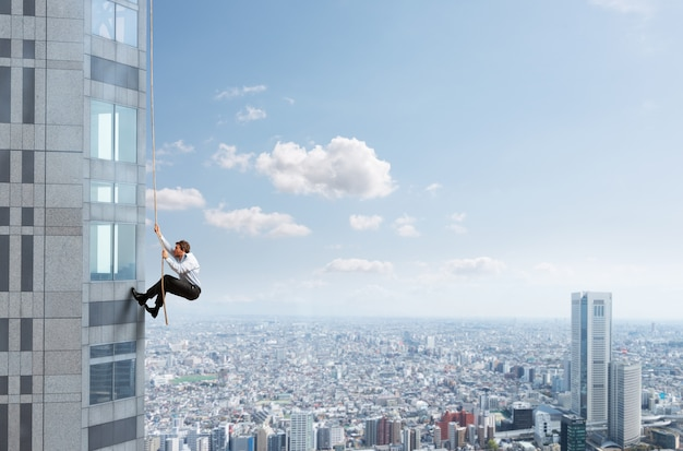 Businessman climbs a high building with a rope. concept of determination