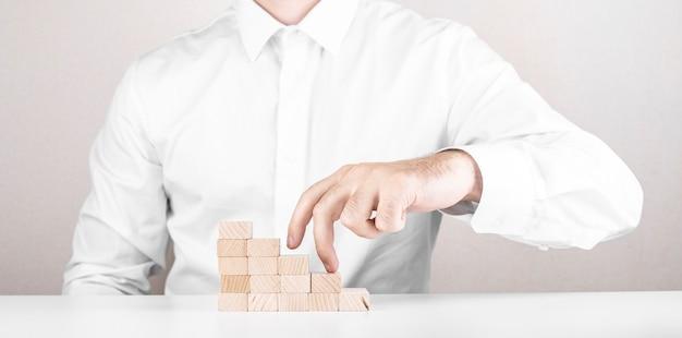 Бизнесмен поднимается по карьерной лестнице. бизнес-концепция из кубиков.