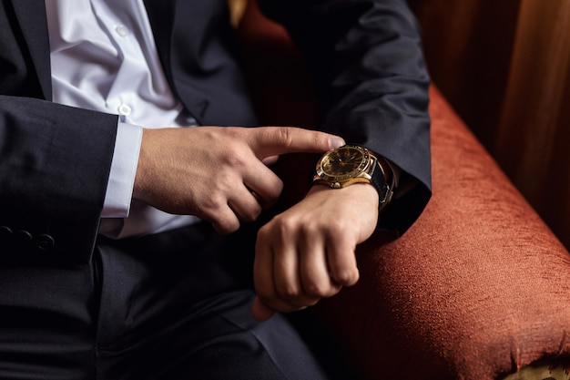 Businessman clock clothes, businessman checking time on his wristwatch. men's hand with a watch, watch on a man's hand, the fees of the groom, wedding preparation, preparation for work