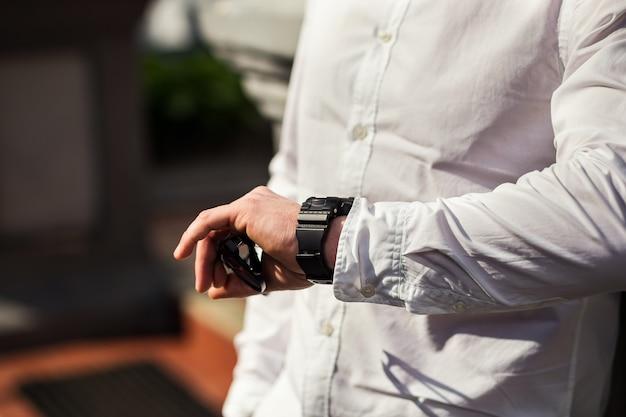 実業家の時計の服、実業家は彼の腕時計で時間をチェックします。時計付きの男性の手、男性の手で見る、新郎の料金、仕事の準備、時計の時計の時間を短くする、男性のスタイル、