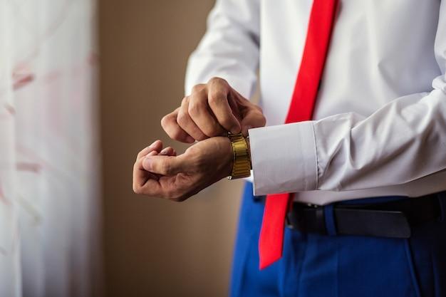 実業家の時計の服、実業家は彼の腕時計で時間をチェックします。時計付き男性の手、男性の手で見る、新郎の料金、結婚式の準備、仕事の準備