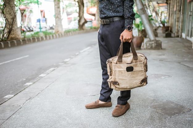 Бизнесмен крупным планом на ноге и держит сумку