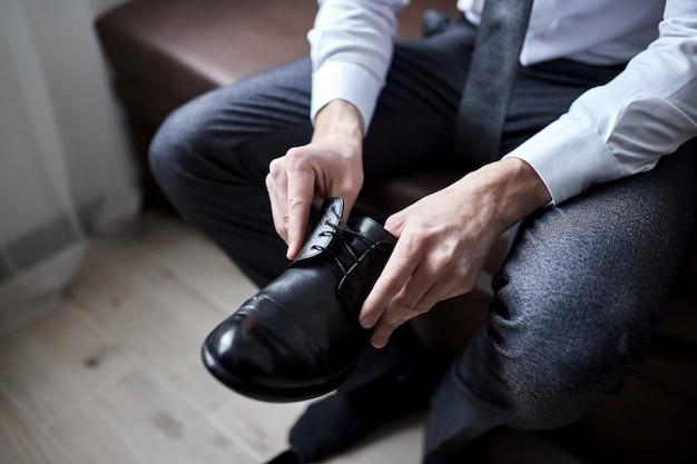 ビジネスマンの服の靴、仕事の準備をしている男性、結婚式の前に新郎の朝。メンズファッション