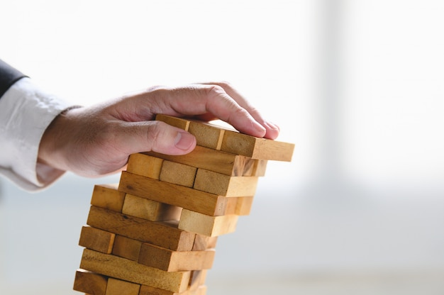 Businessman collapsing stacked tower wood block by hand as failure or bankrupt project.